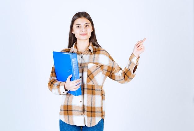 Mooie vrouwelijke werknemer met blauwe map die aan haar zijde wijst.