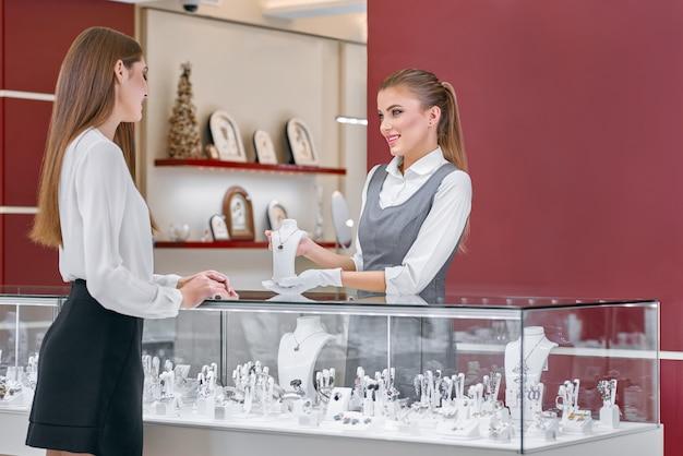 Mooie vrouwelijke werknemer van een juwelierszaak die een halsband toont aan een vrouw dichtbij de teller