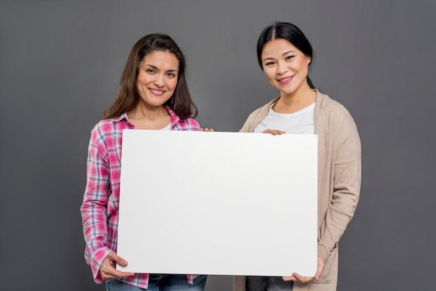 Mooie vrouwen blanco vel papier houden