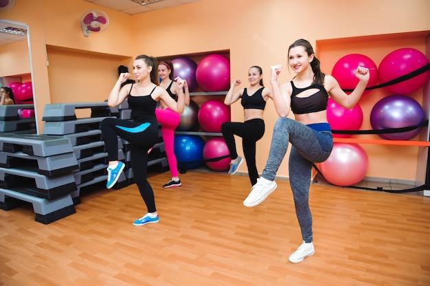 Mooie vrouwen die aerobics in geschiktheidsclub uitoefenen.