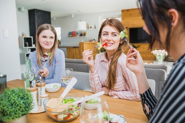 Mooie vrouwen die bij lijst en het glimlachen eten