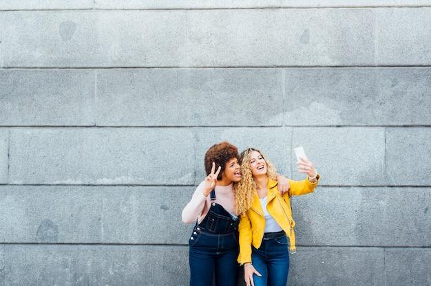 Mooie vrouwen die een zelfportret nemen op de straat. lgtb-concept