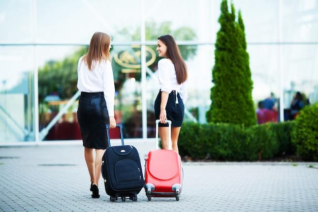 Mooie vrouwen die graag met koffers reizen in de buurt van de luchthaven