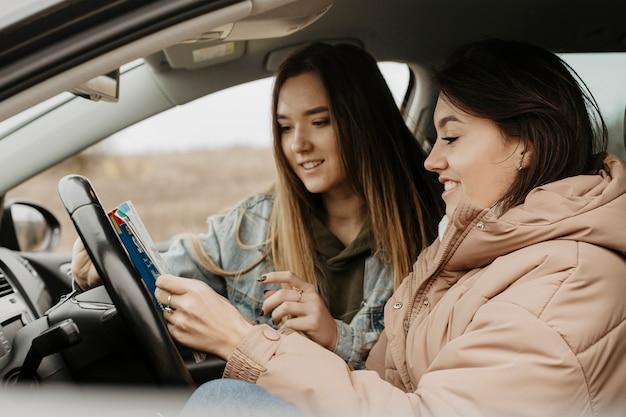 Mooie vrouwen die het zijaanzicht van de reiskaart controleren
