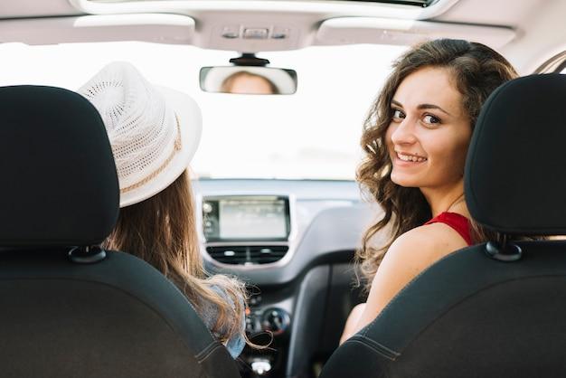 Mooie vrouwen die in auto en het drijven zitten