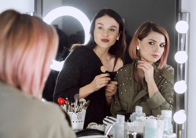 Mooie vrouwen die in de spiegel kijken