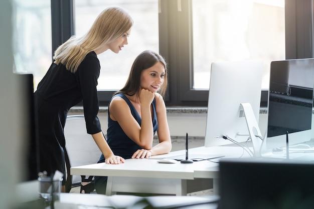 Mooie vrouwen die in het bureau aan een computer samenwerken