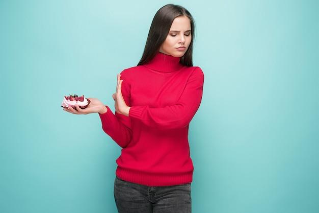 Mooie vrouwen die kleine cake houden. verjaardag, vakantie, dieet. studioportret over blauwe achtergrond