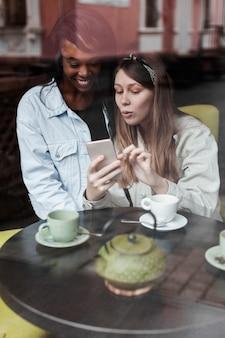 Mooie vrouwen die mobiele telefoon bekijken