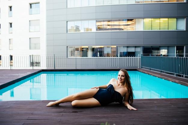 Mooie vrouwen die ontspannen bij het luxe zwembad. meisje bij het zwembad van het reiskuuroord. luxe zomervakantie.