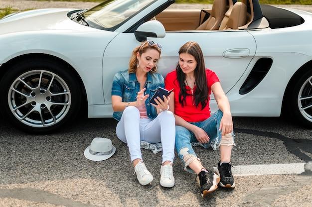 Mooie vrouwen die op auto leunen