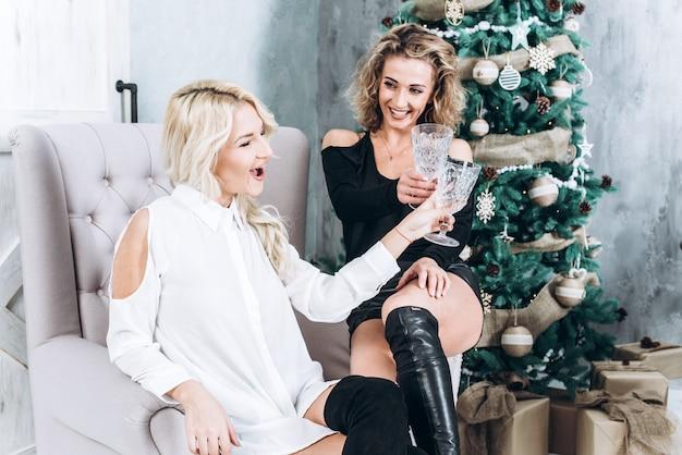 Mooie vrouwen die pret met champagne in nieuw jaarbinnenland hebben
