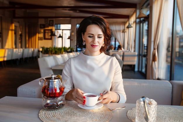 Mooie vrouwen die thee drinken in gezellig café. ondernemers nemen een pauze met een theekopje. lichte lifestyle foto in een stijlvol café.