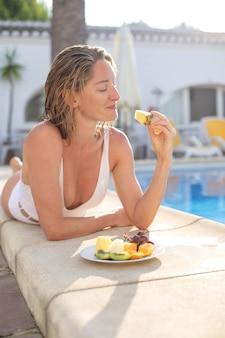 Mooie vrouwen die vers fruit eten, liggend op de richel van het zwembad