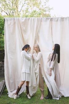 Mooie vrouwen die zich in witte kleding in tuin bevinden.