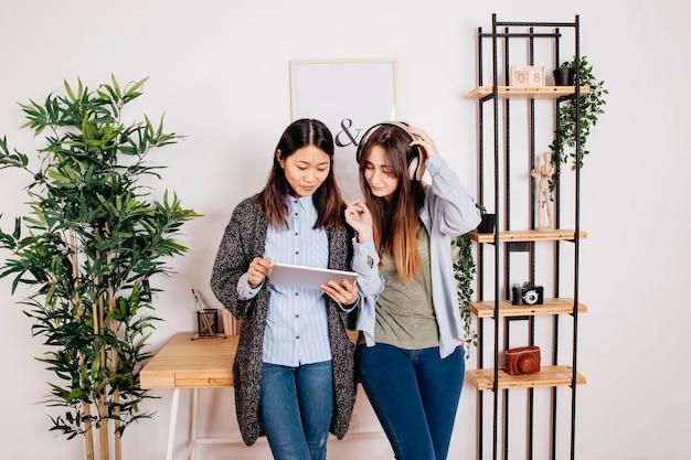 Mooie vrouwen die zich met digitale tablet bevinden