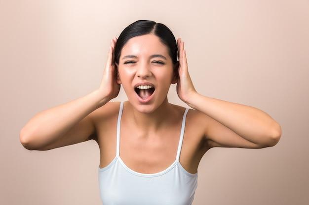 Mooie vrouwen gefrustreerd door lawaai dat haar gilt en bedekt