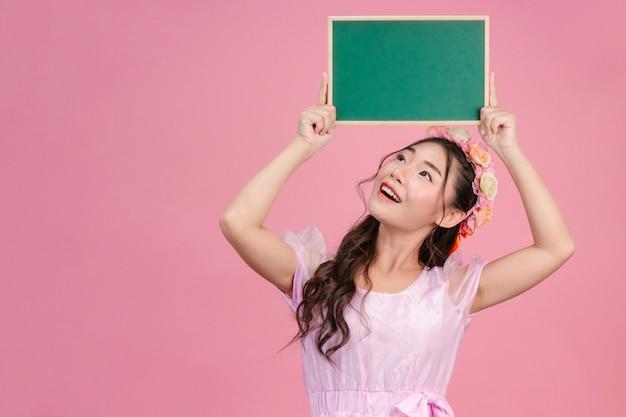 Mooie vrouwen gekleed in roze prinses jurken houden een groen bord op een roze.