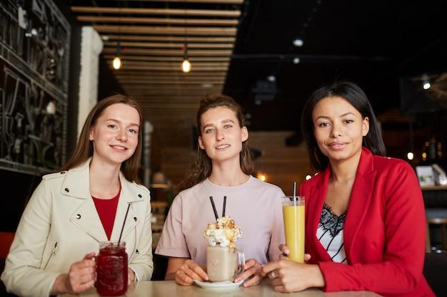 Mooie vrouwen genieten van zoete drankjes in café
