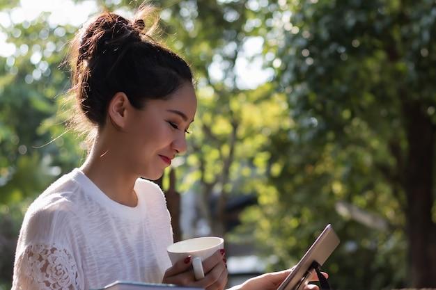 Mooie vrouwen hebben genoten in de tuin met koffie en tablet