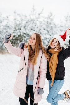 Mooie vrouwen in kerstmanhoed die selfie in de winterbos nemen