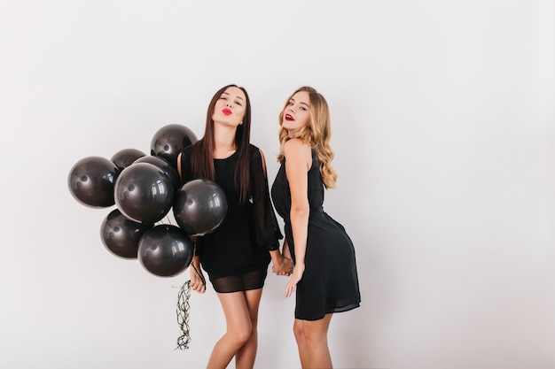 Mooie vrouwen in soortgelijke jurken hand in hand en poseren met kussende gezichtsuitdrukking op feestje