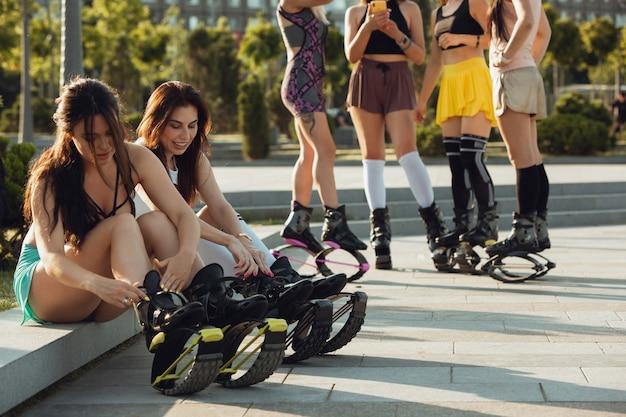 Mooie vrouwen in sportkleding springen in een kangoo springt schoenen op straat op een zonnige dag.