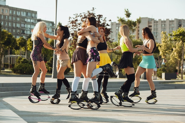 Mooie vrouwen in sportkleding springen in een kangoo springt schoenen op straat op zonnige zomers