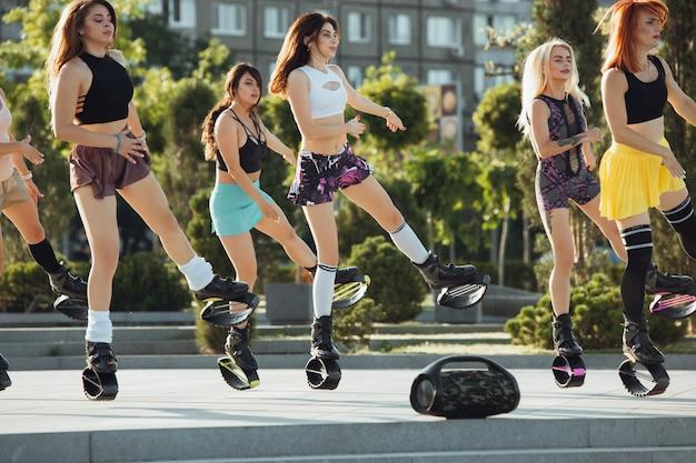 Mooie vrouwen in sportkleding springen in een kangoo springt schoenen op straat