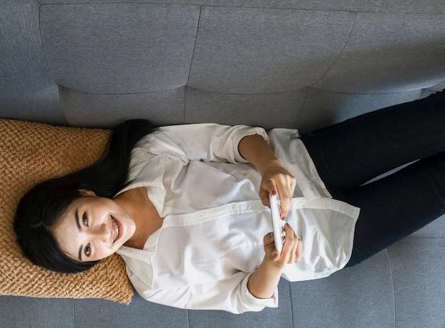 Mooie vrouwen in witte jurken gebruiken mobiele telefoons online op de bank. online winkelconcept