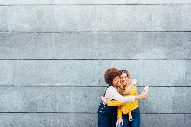 Mooie vrouwen met behulp van een mobiele telefoon op straat. lgtb-concept