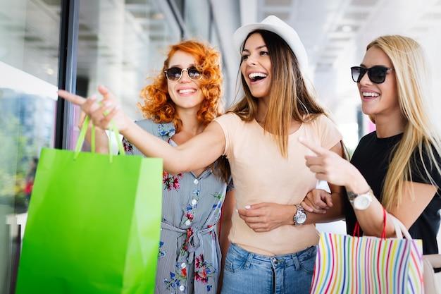Mooie vrouwen met boodschappentassen wandelen in het winkelcentrum