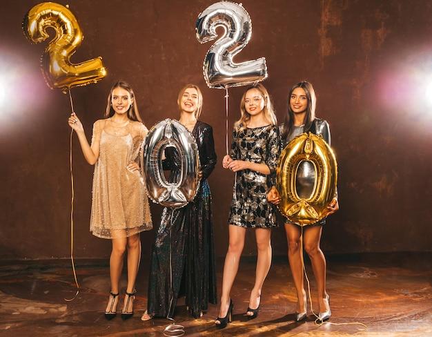 Mooie vrouwen nieuwjaar vieren. gelukkige prachtige meisjes in stijlvolle sexy feestjurken met gouden en zilveren 2020-ballonnen, plezier op oudejaarsfeest. vakantieviering. charmante modellen