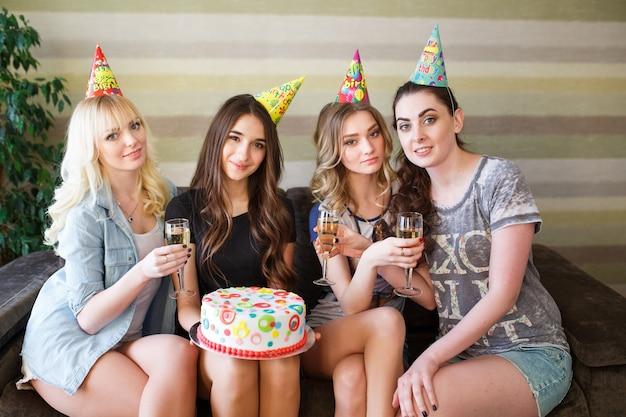 Mooie vrouwen poseren met cake op verjaardagsfeestje