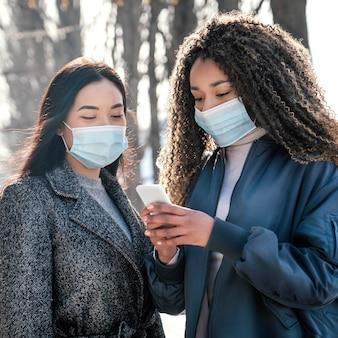 Mooie vrouwen poseren samen met masker Premium Foto
