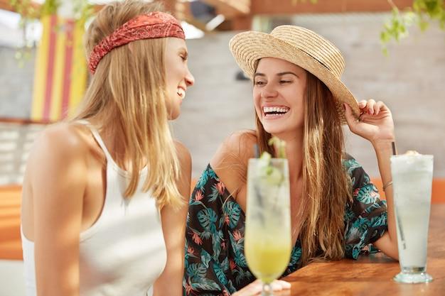 Mooie vrouwen recreëren samen in een koffieshop, drinken verse cocktails. ontspannen schattige vrouwtjes ontspannen tijdens de zomervakantie.