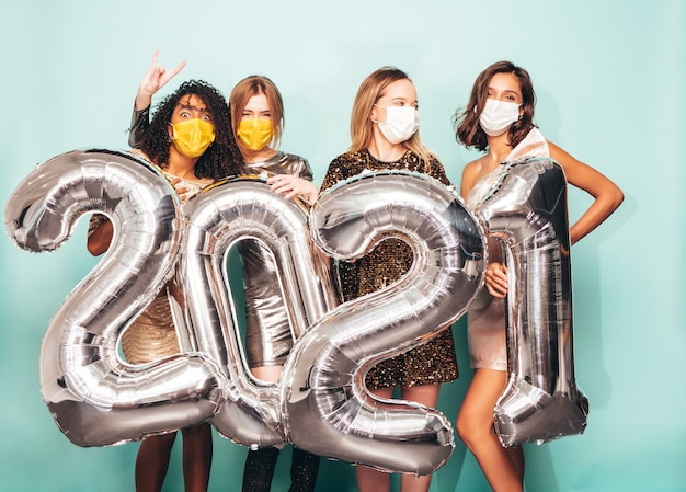 Mooie vrouwen vieren nieuwjaar. gelukkige prachtige vrouw in stijlvolle sexy feestjurken met zilveren ballonnen uit 2021, plezier makend op oudejaarsavond. feestdagen