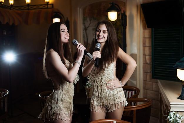 Mooie vrouwen zingen karaoke liedjes in microfoons in restaurant