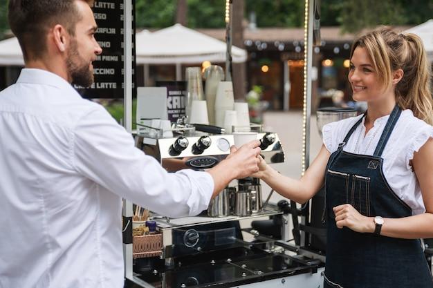Mooie vrouwenbarista die koffie verkoopt aan de klant in het straatkoffie