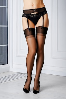 Mooie vrouwenbenen in ouderwetse kousen zonder elastan, jarretellegordel en slipje