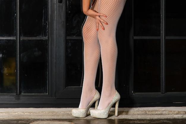 Mooie vrouwenbenen in witte kousen op hoge hielen die zich op vensterbank bevinden