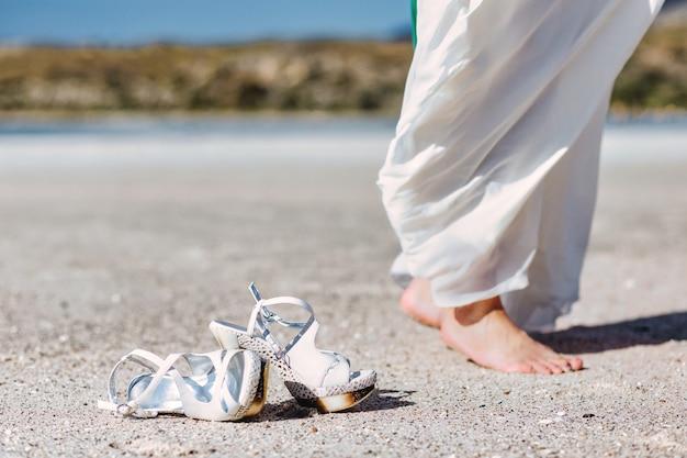Mooie vrouwenbenen op de strandvoeten die op het zand lopen