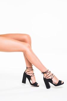 Mooie vrouwenbenen op hielen die op witte muur worden geïsoleerd