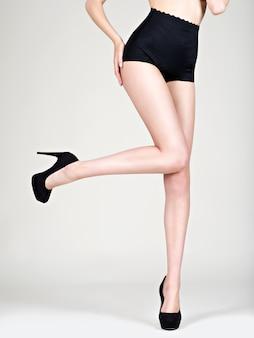 Mooie vrouwenbenen op hoge hakken, zwarte slipjes -