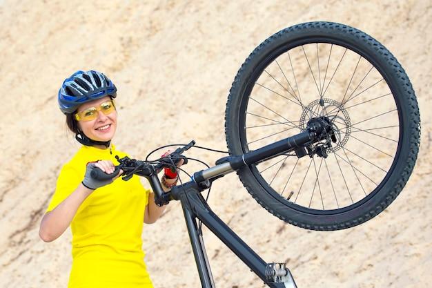 Mooie vrouwenfietser met fiets tegen de achtergrond van het zand. sport en recreatie. natuur en mens