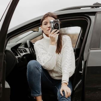 Mooie vrouwenfotograaf die door camera kijkt