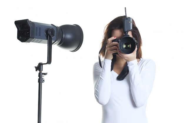 Mooie vrouwenfotograaf die in studio werken