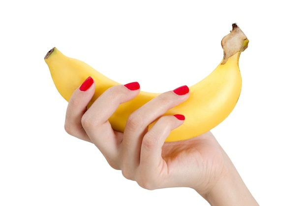 Mooie vrouwenhand met de rode die banaan van de spijkerholding op witte achtergrond wordt geïsoleerd