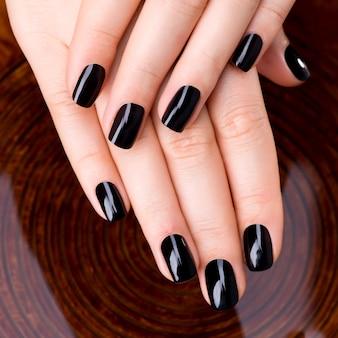 Mooie vrouwenhanden met zwarte manicure na kuuroordprocedures - kuuroordbehandeling concept