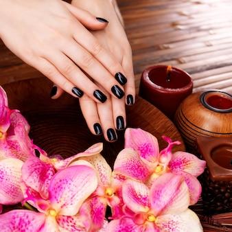 Mooie vrouwenhanden met zwarte manicure na kuuroordprocedures - kuuroordbehandelingconcept